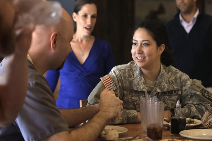 Brown University student and U.S. Army ROTC cadet Maddy Gonzalez, of Tacoma, Wash., in uniform at center right, speaks with U.S. Navy veteran and Brown student Chris Baker, of Warwick, R.I., second from left, during a luncheon at a pizza restaurant near Brown's campus, in Providence, R.I. The luncheon was hosted by the university to make student veterans more welcome on campus. Karen McNeil, Brown University program director in the office of student veterans and commissioning programs, looks on behind left