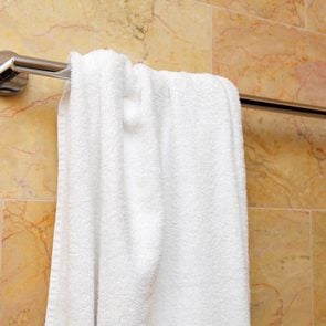 white bath towel hanging on a towel rod in the bathroom