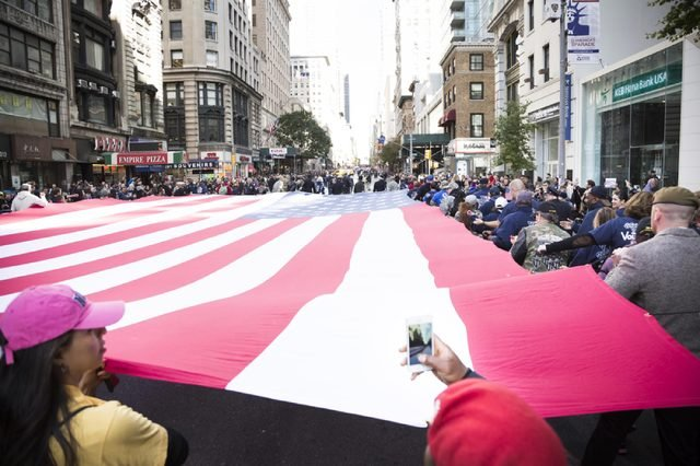 NEW YORK - 11 NOV 2016: Vets and military personnel carry a large American Flag from TheGroundZeroFlag.com in the annual Americas Parade up 5th Avenue on Veterans Day in Manhattan.