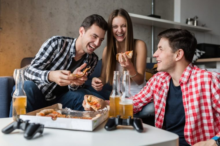 happy young people eating pizza, drinking beer, having fun, friends party at home, hipster company together, two men one woman, smiling, positive, relaxed, hang out, laughing, funny emotions