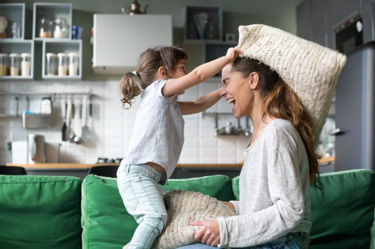 Mommy and kid daughter having pillow fight together, young babysitter nanny playing funny game with kid girl at home, happy mother and child enjoy spending time together, family leisure fun activity