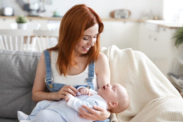 Happy motherhood concept. Picture of cute joyful young European mom with ginger hair babysitting adorable infant at home, enjoying maternity leave, bonding with her baby, having cheerful smile
