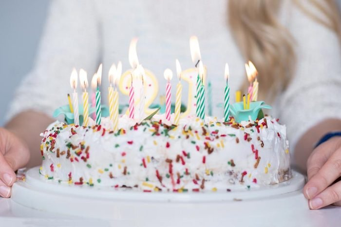 Portrait of a young beautiful blond girl holding plate with birthday cake and blowing candles making a wish