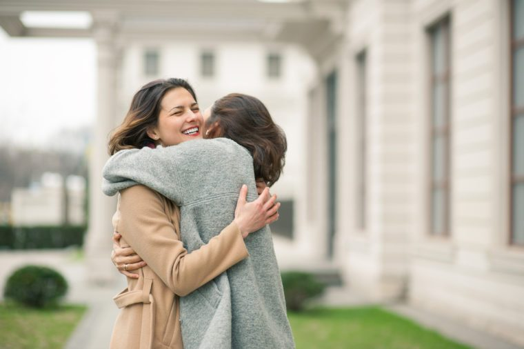 Two girls hug on the sidewalk. Feel joyfull and happy together.