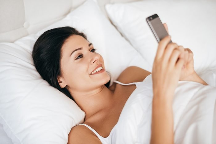 Always available for him. Beautiful young woman smiling and holding smart phone while lying in the bed at home