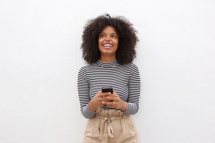Portrait of happy african american woman holding smart phone