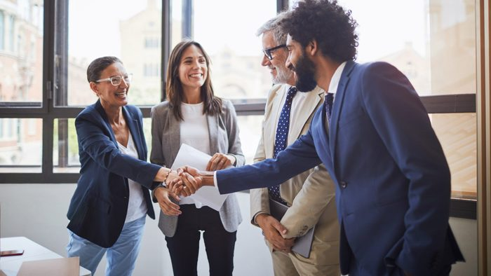 men and women shaking hands in an office. dressed in business casual. best places to work.