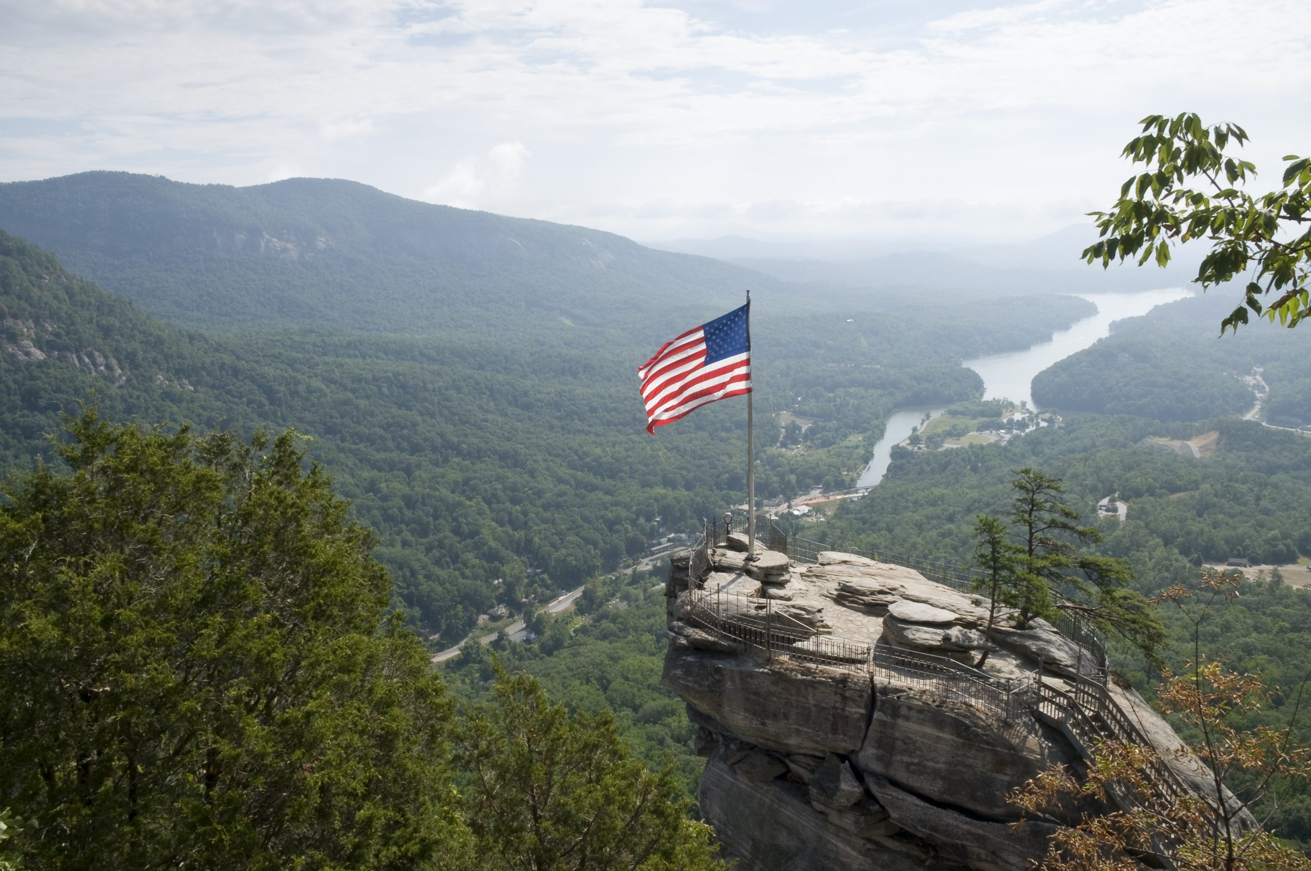 aerial shot of the top of Chimney Rock, North Carolina, with a waving American flag, and Lake Lure in the background among the Blue Ridge Mountains