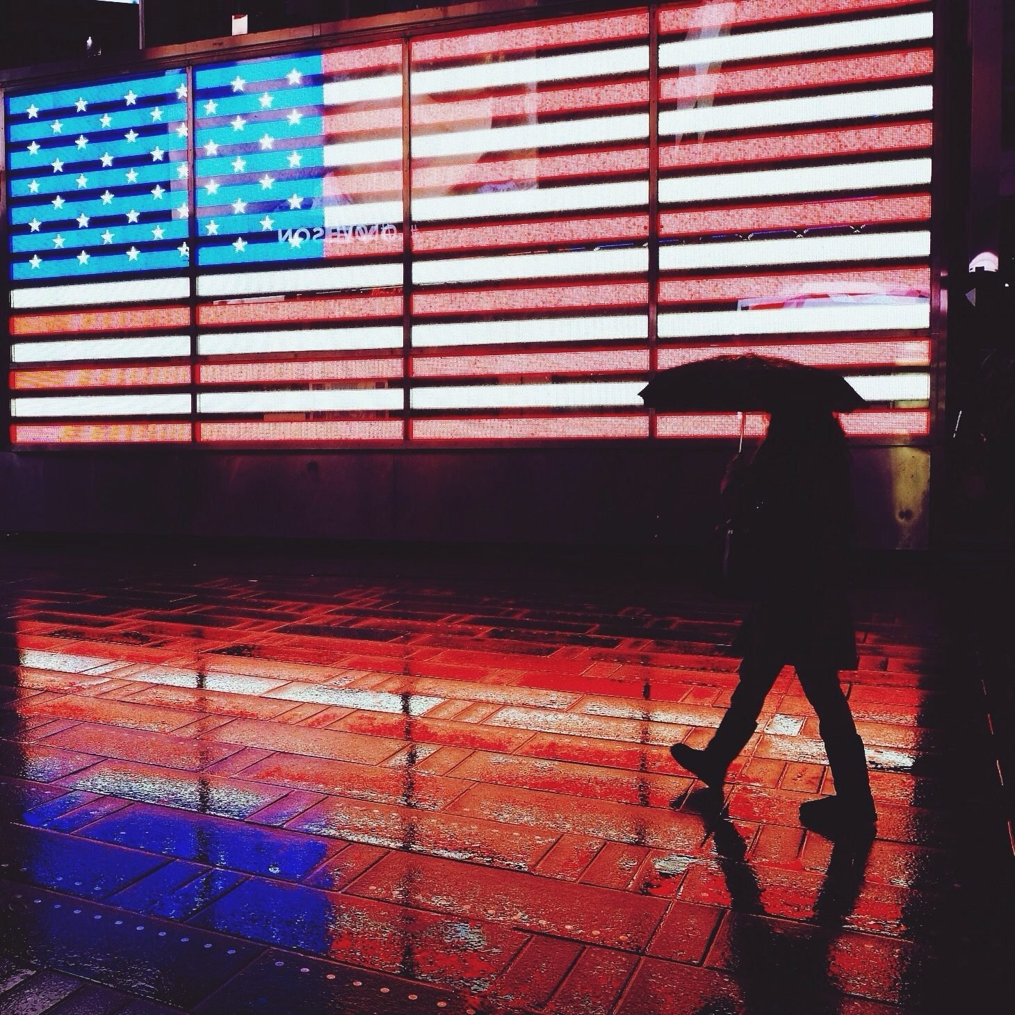 a silhouetted figure holding an umbrella walks past an LED american flag in times square, new york city, on a rainy night