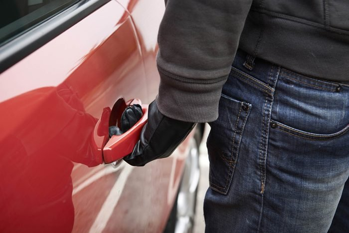 a theif's gloved hand on the door handle of a stolen red car