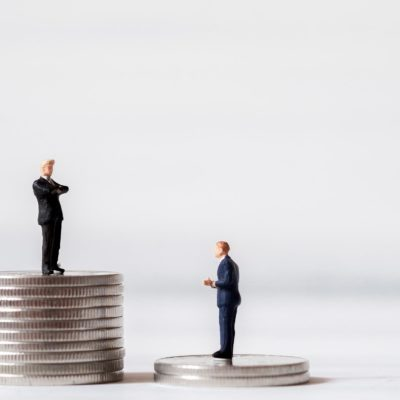 Miniature business people stand on pile of money coin. Cash is king financial concept and more buy power.