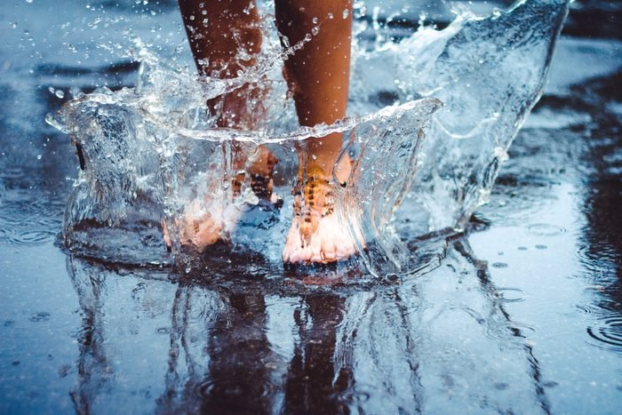 Unrecognizable person (female) is splashing water in a puddle on a rainy day in the city. Legs in puddle.; Shutterstock ID 405646975; Job (TFH, TOH, RD, BNB, CWM, CM): -