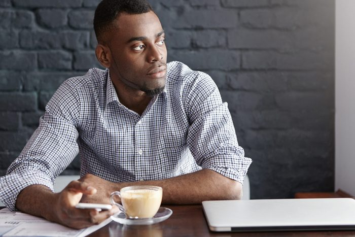 Attractive young African-American entrepreneur typing sms on smart phone with thoughtful and serious look, sitting alone at cafe table with mug, papers and laptop computer, waiting for his lunch