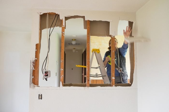 Female construction worker and homeowner using a sawsall tool to cut drywall out and take a wall down to a half-wall during a DIY house renovation.