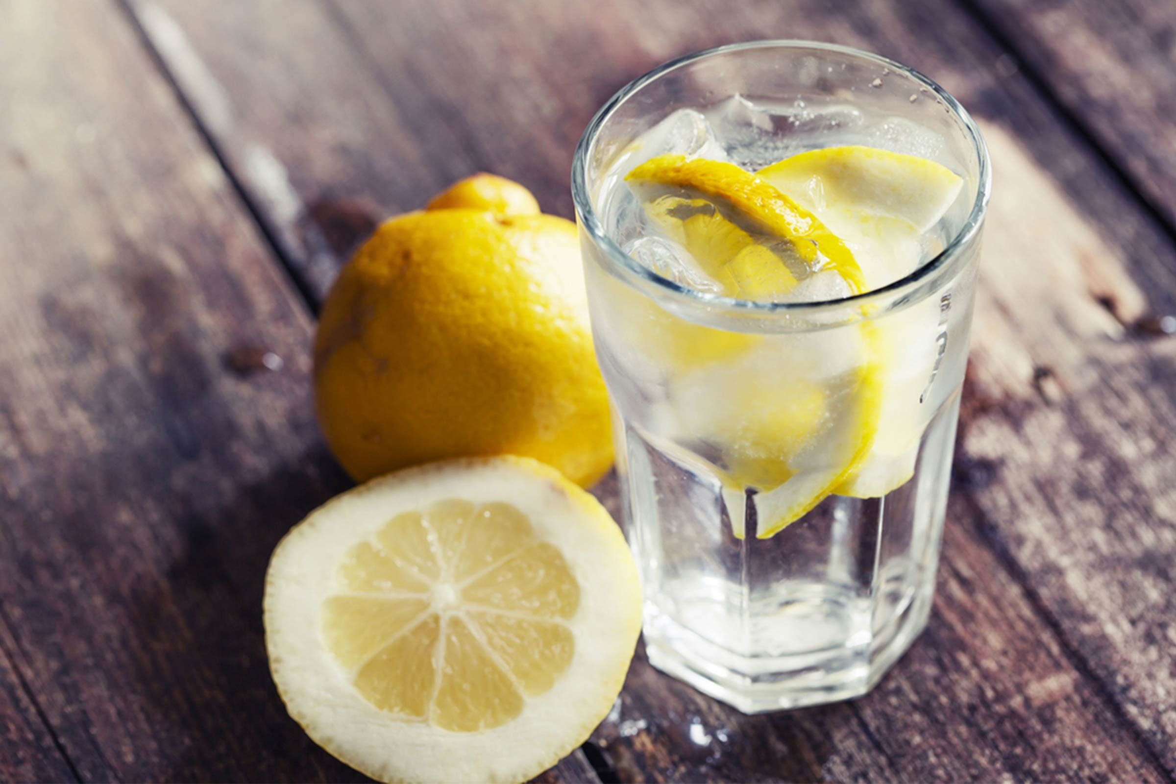 lemon water in clear glass with lemons on rustic wooden table