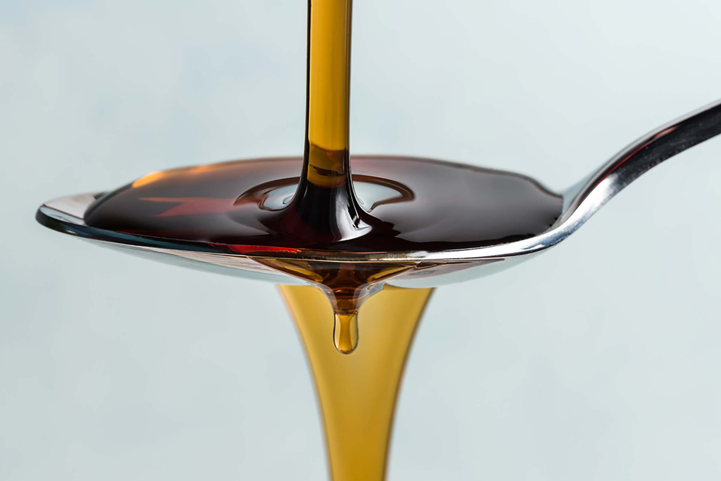 Molasses pouring into a tablespoon