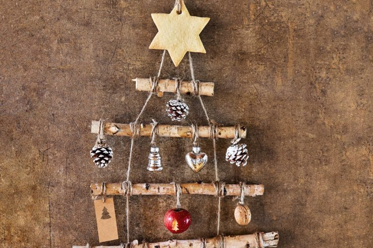 Homemade rustic Christmas tree decoration made from sticks and ornaments with large six pointed star on top