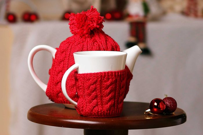 A cup and tea-pot is in New-year scenery. Decorated the knitted scarf and cap create the atmosphere of heat, comfort, holiday