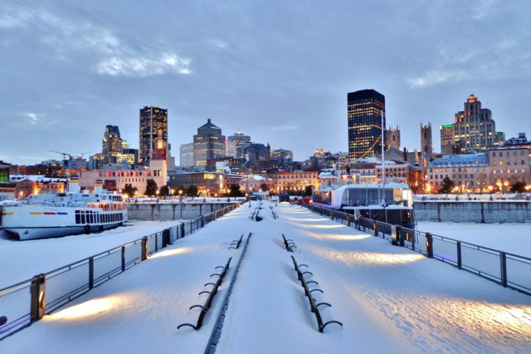 Snow-covered benches, pier, waterfront walkway, harbour, and downtown Montreal after sunset in winter - Montreal, Canada