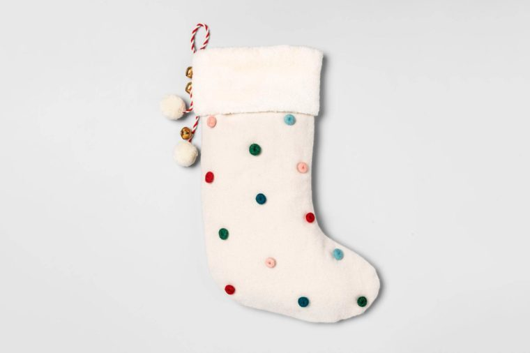 white stocking with pom poms on grey background