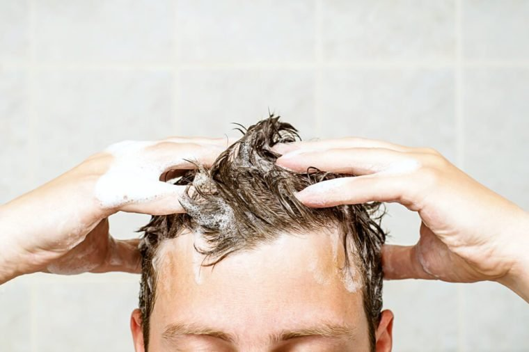young man washing his hair, taking a shower with foam on his head holds fingers in hair in bathroom