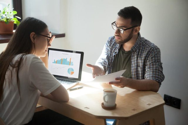 Two millennial coworkers having argument and business dispute in office. Businessman showing businesswoman paper document with working problems