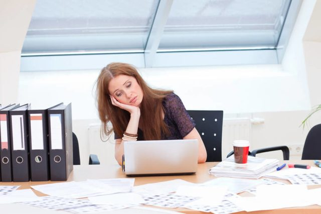 bored business woman is almost falling from her chair