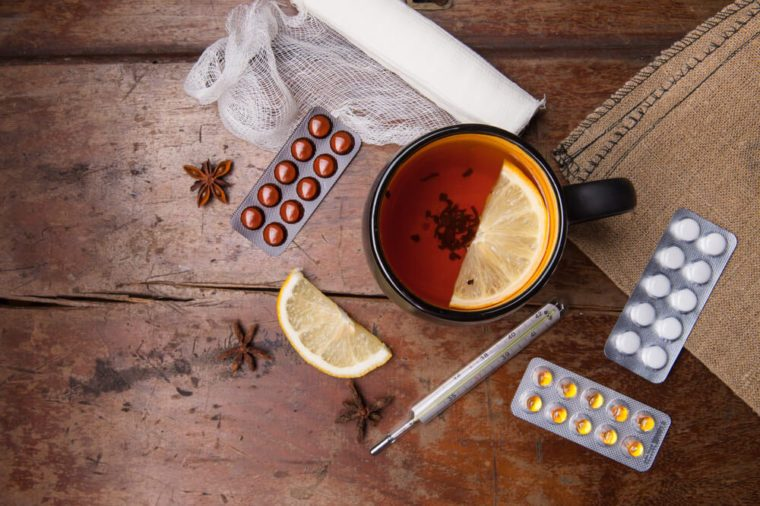 Seasonal flu: pills, thermometer and tea with lemon. View from above