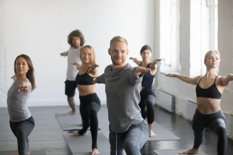 Group of young sporty smiling people practicing yoga lesson with instructor, standing in Warrior Two exercise, Virabhadrasana 2 pose, working out, indoor close up image, studio. Wellbeing concept