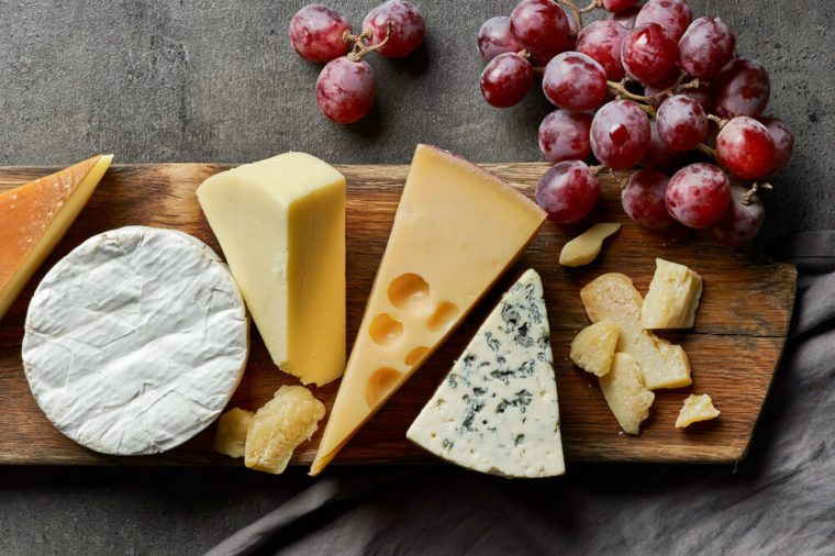 various types of cheese on wooden cutting board, top view
