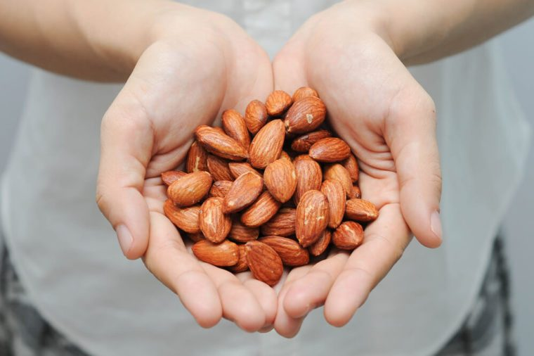 Almond nuts in the woman's hands