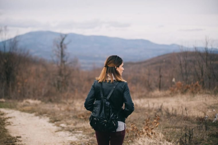Girl with a black leather backpack exploring the nature.