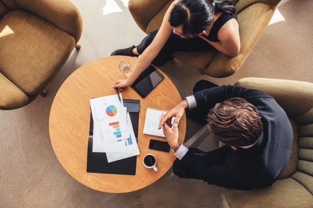 Top view of business colleague sitting at table with charts during corporate meeting. Businessman and businesswoman discussing new project while sitting in office lobby.