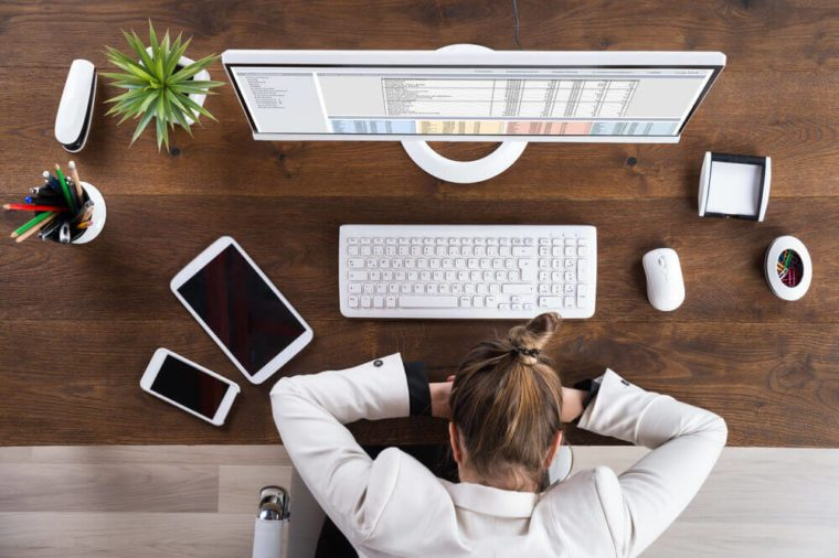 Young Businesswoman Sleeping On Desk At Workplace
