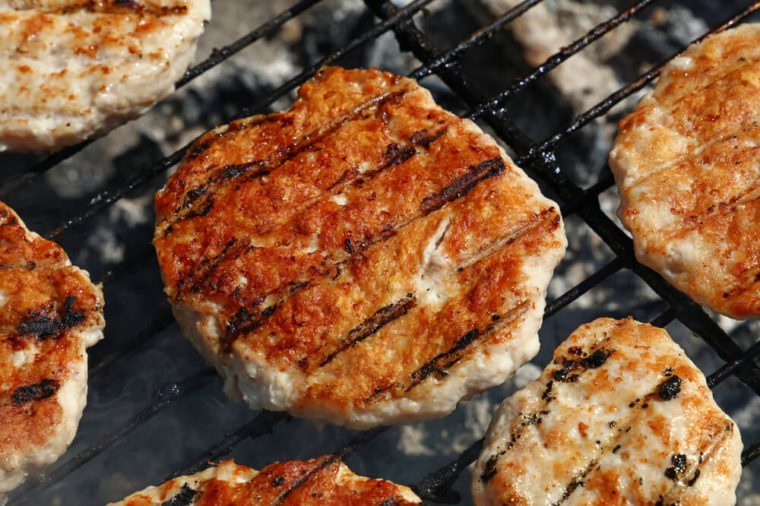 Chicken or turkey poultry meat barbecue grilled burgers for hamburger prepared on bbq smoke grill, close up