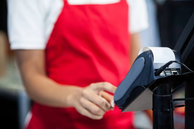 Mid section of female staff using credit card terminal at cash counter in supermarket