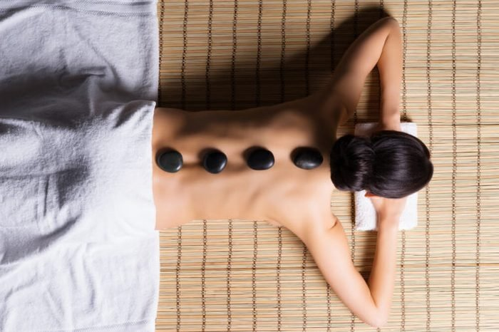 Beautiful, young and healthy woman on bamboo mat in spa salon is having hot stone massage. Spa, health and healing concept.