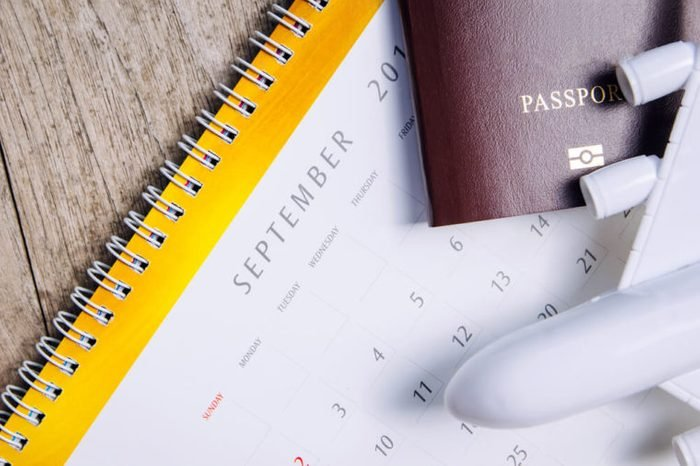 airplane and passport on calendar background for summer trip , Travel with an airplane , travel plan concept.