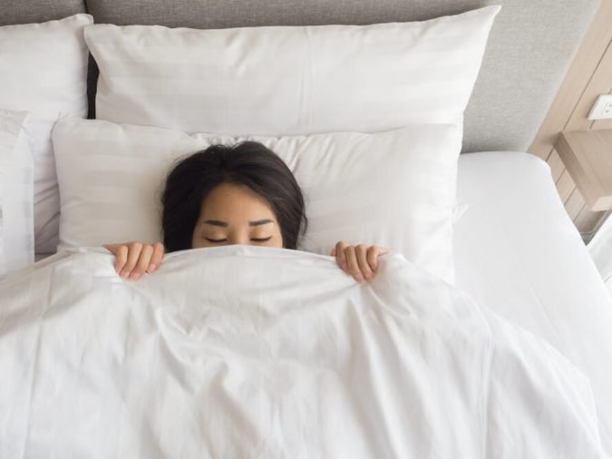 Sleeping woman cover face with blanket flat lay. Close-up of young women, sleeping under white blanket and covering half face.