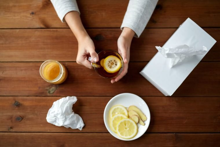 woman drinking tea with lemon, honey and ginger and paper wipes box on wooden table