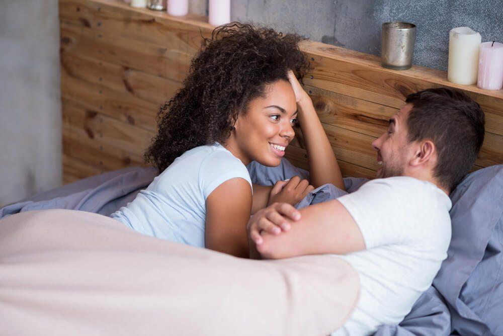 Sweet couple talking in bed on their honeymoon