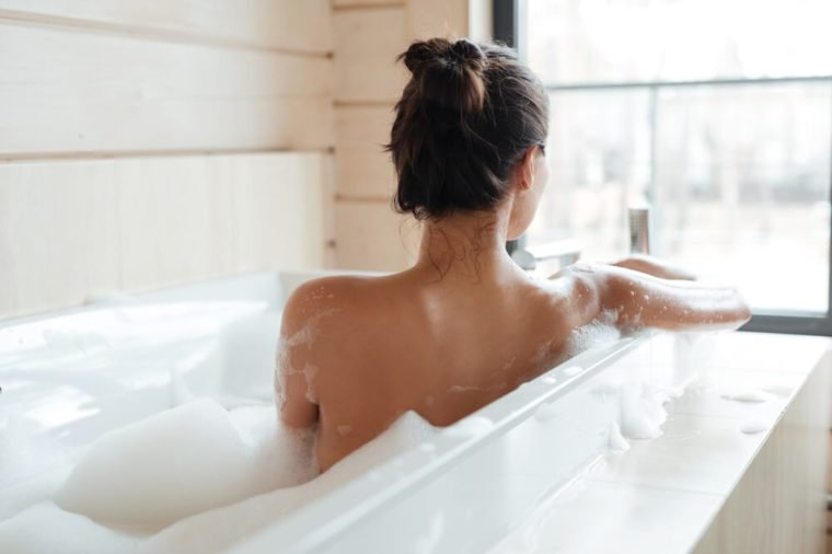 Back view of a young woman having bubble bath and looking at window