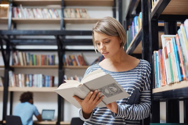 Portrait of charming blonde student girl with short hair in casual clothes standing near shelf in library, reading book, looking through information about economic systems.