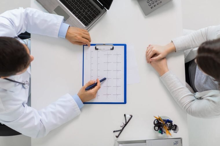 medicine, healthcare, cardiology and people concept - doctor with cardiogram on clipboard and young patient woman meeting at hospital