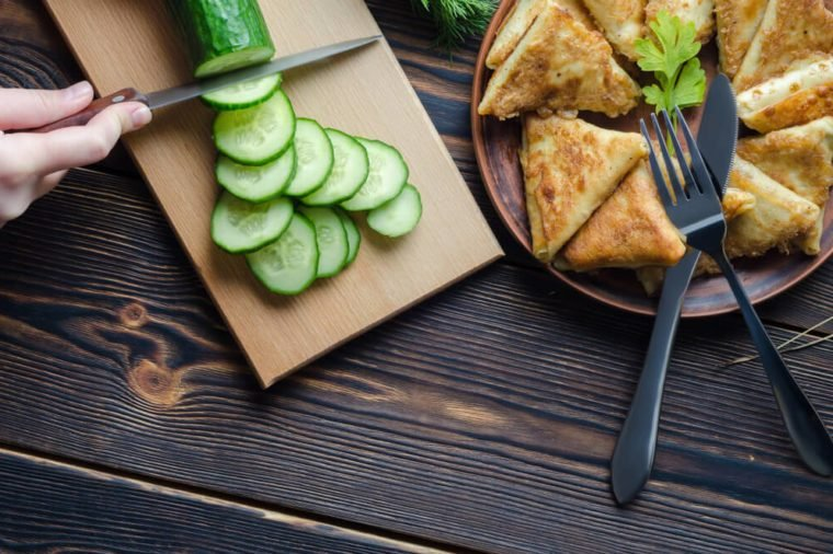 Crop view from above of person cutting cucumber into rounds on wooden board with snack plate near.