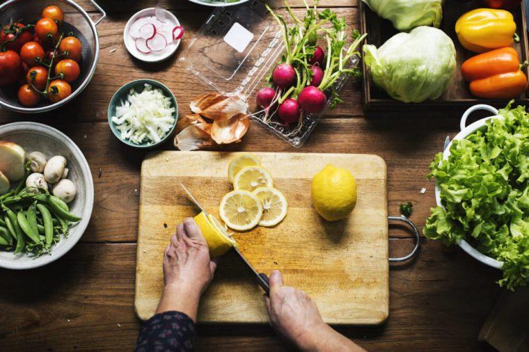 Hands using a knife chopping lemon