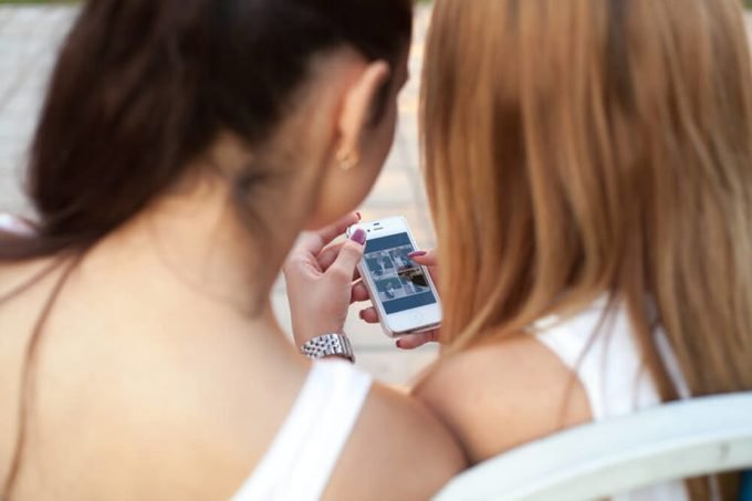 Two cute beautiful young women friends sitting on park bench on summer day, browsing pictures on smartphone, back view, focus on device screen