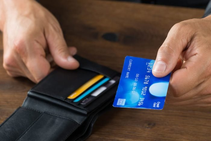 Cropped image of businessman giving credit card from wallet at desk