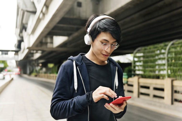 Asian guy listening music by headphones