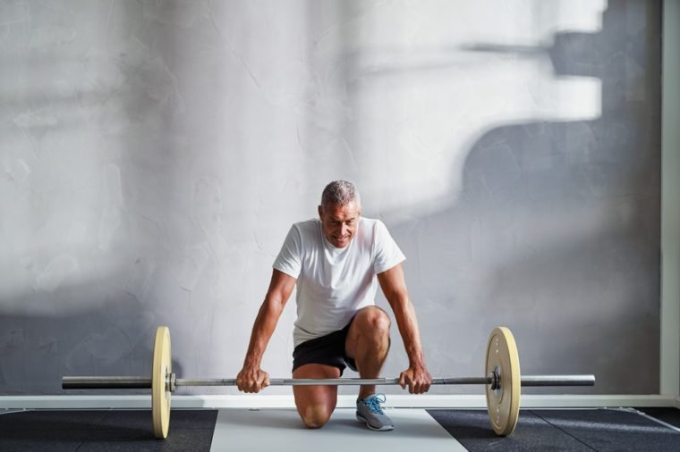 Focused senior man in sportswear kneeling alone in a gym preparing to lifting weights during a workout